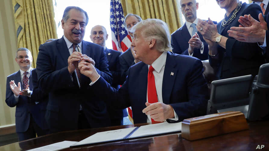 FILE - President Donald Trump gives the pen he used to sign an executive order to Dow Chemical President, Chairman and CEO Andrew Liveris, as other business leaders applaud in the Oval Office of the White House in Washington. Dow Chemical is pushing...