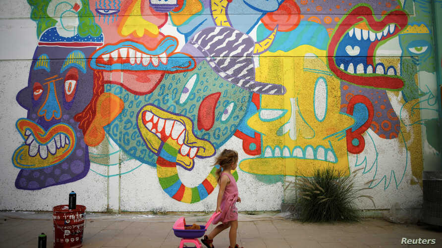 A girl looks at a wall painting by Israeli artist who goes by the name Dioz, during an art happening, called POW! WOW! Israel, which is connected to a week-long art and culture festival held in Hawaii called POW! WOW! Hawaii, in the southern city of