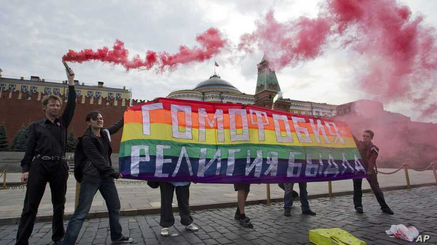 Gay rights activists hold a banner reading 'Homophobia - the religion of bullies' during their action in protest at homophobia, on Red Square in Moscow, Russia, July 14, 2013.