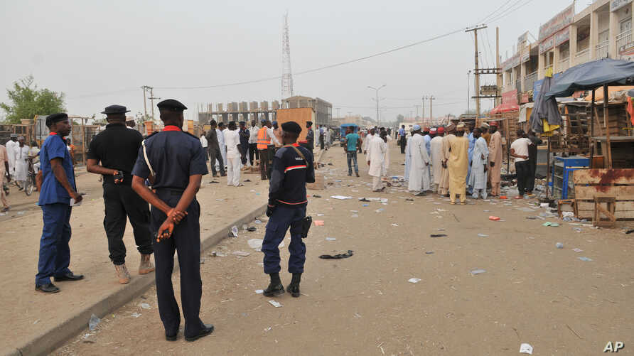 Security officers stand guard at the scene of an  explosion at a mobile phone market in Kano, Nigeria. Wednesday Nov. 18, 2015.