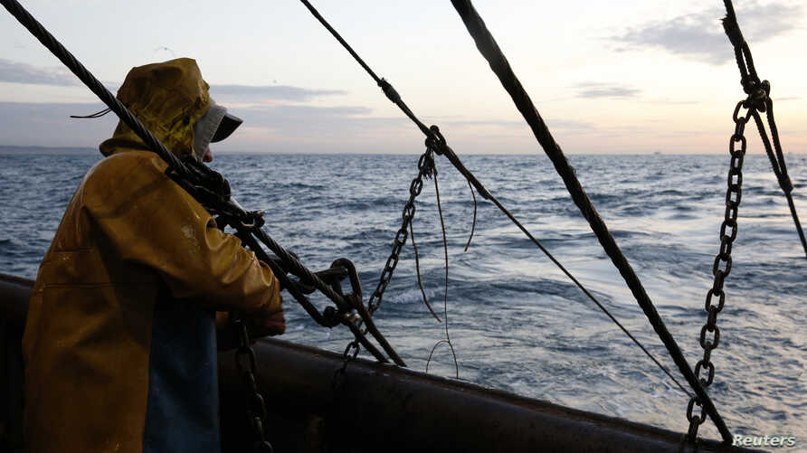 FILE - A fisherman on a Boulogne sur Mer-based trawler prepares to raise fishing nets off the coast of northern France, Oct. 21, 2013.