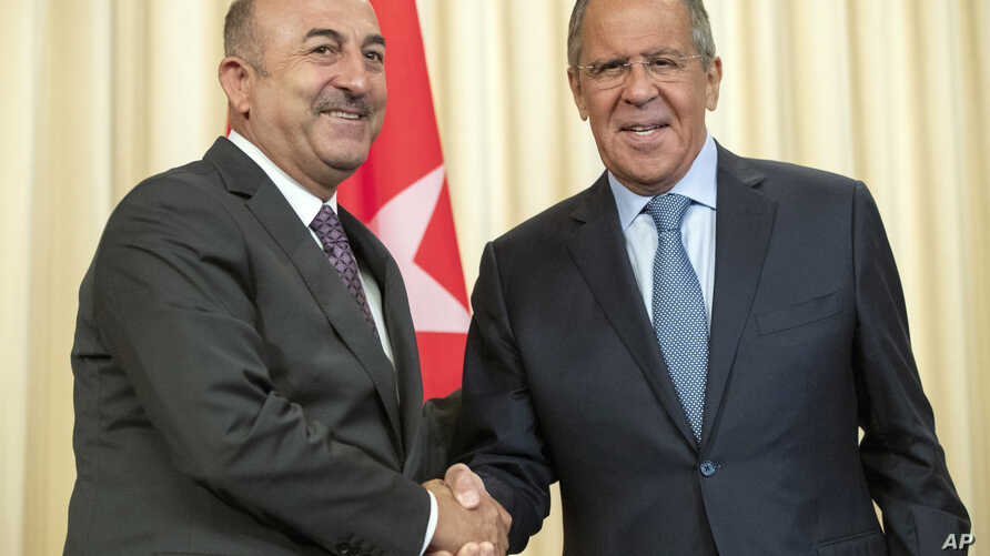 Russian Foreign Minister Sergey Lavrov, right, and his Turkish counterpart Mevlut Cavusoglu shake hands during their meeting in Moscow, Russia, Aug. 24, 2018.