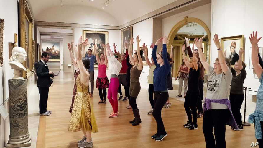 FILE - An exercise group works in front of a bust of Benjamin Franklin at the Metropolitan Museum of Art in New York, Feb. 10, 2017.