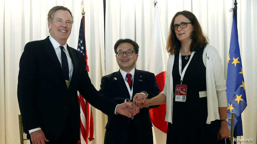 U.S. Trade Representative Robert Lighthizer, Japanese Minister of Economy,Trade and Industry Hiroshige Seko and European Commissioner for Trade Cecilia Malmstrom pose for a photo during a meeting at the 11th World Trade Organization's ministerial con