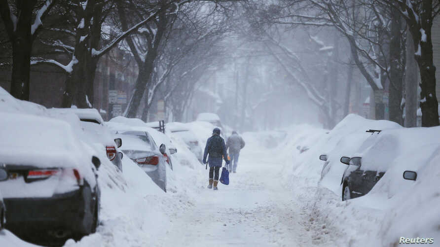 Pedestrians make their way along a snow covered street during a winter snow storm in Cambridge, Massachusetts, Feb. 9, 2015.