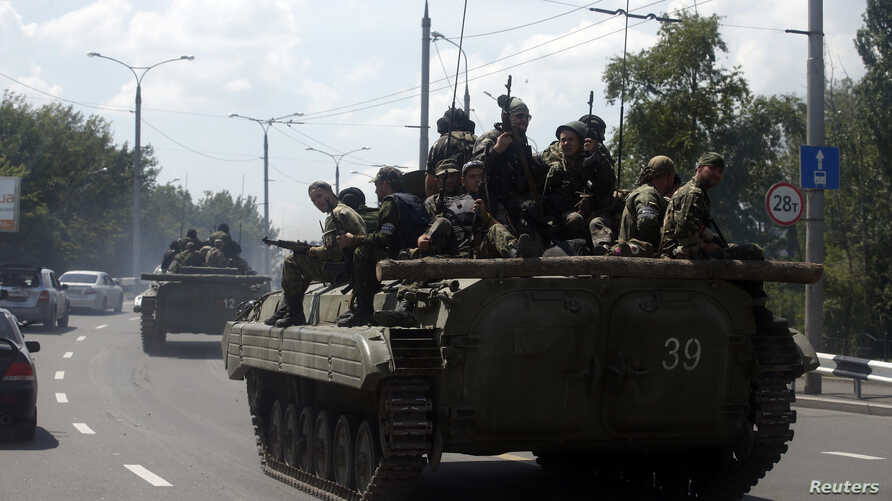 Pro-Russian separatist fighters are seen on armored vehicles in the eastern Ukrainian city of Donetsk, July 10, 2014.