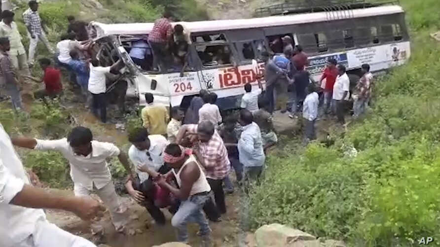 In this grab made from video provided by KK Productions, rescuers pull out passengers from a bus that fell into a gorge in Jagtiyal district of Telangana, India, Sept. 11, 2018.