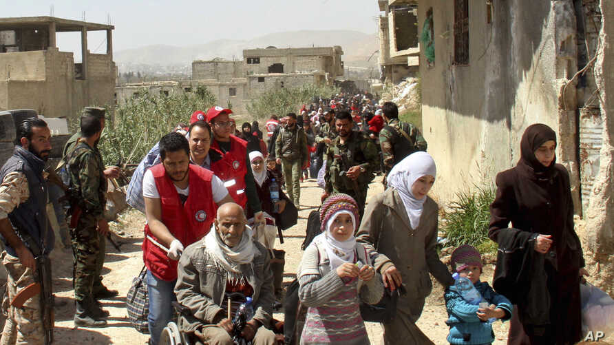 This photo, released by the Syrian official news agency SANA, shows civilians carrying their belongings leaving towns and villages, in the eastern Ghouta region near Damascus, Syria, March. 25, 2018.