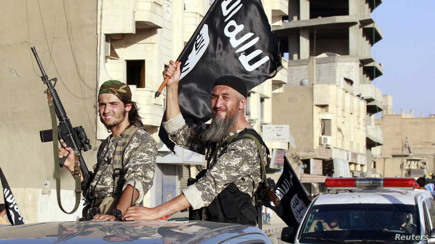 Militant Islamist fighters wave flags as they take part in a military parade along the streets of Syria's northern Raqqa province, June 30, 2014.