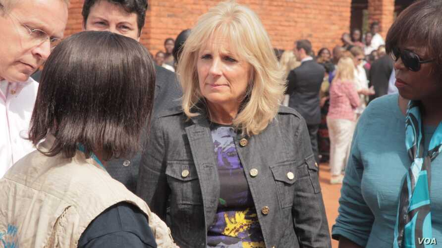 Dr. Jill Biden and World Food Program Executive Director Ertharin Cousin are briefed by a WFP worker in Zomba district, Malawi, on the progress of school feeding program, July 19, 2015. (VOA/L. Masina)