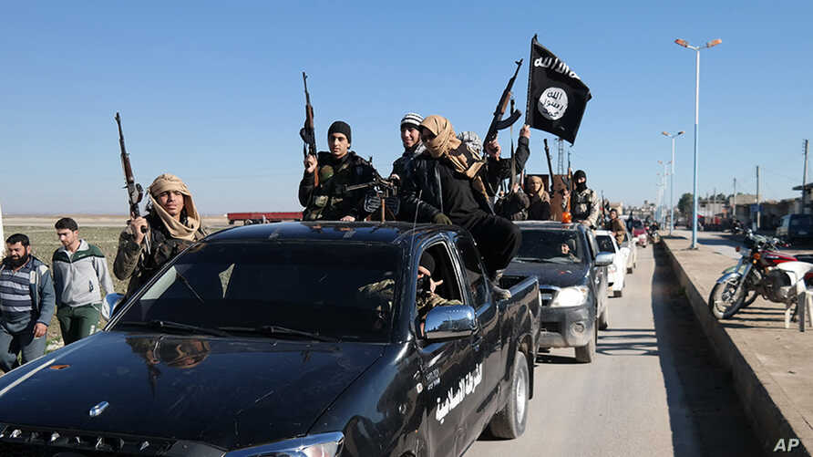 In this photo released on May 4, 2015, by a militant website, which has been verified and is consistent with other AP reporting, Islamic State militants pass by a convoy in Tel Abyad town, northeast Syria.