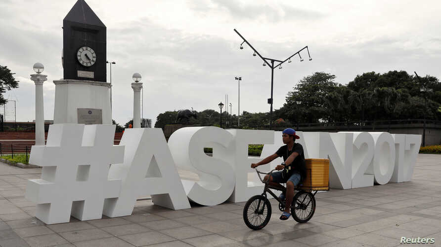 A man rides his bicycle past the ASEAN logo ahead of the 50th ASEAN Foreign Ministers meeting in Manila, Philippines, Aug. 2, 2017.