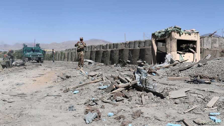 FILE - Afghan security forces inspect the aftermath of a suicide bomb blast in Gardez, Paktia Province, Afghanistan, June 18, 2017.