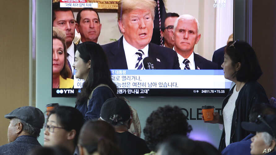 People pass by a TV screen showing a footage of U.S. President Donald Trump during a news program at the Seoul Railway Station in Seoul, South Korea, May 25, 2018.
