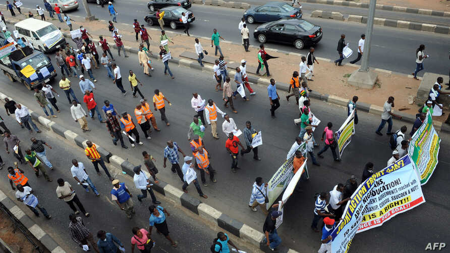 FILE - Students and workers carry placards as they march on the Lagos-Ikorodu highway to protest against the suspension of academic activities following a nation-wide strike embarked by lecturers in state-owned universities in Lagos.