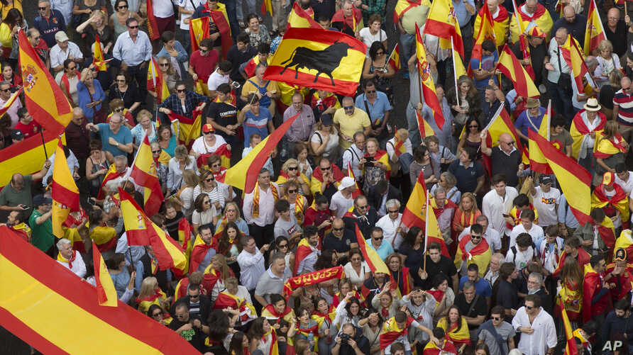 People wave Spanish national flags as thousands packed the central Cibeles square to in Madrid, Spain, Saturday, Sept. 30, 2017.