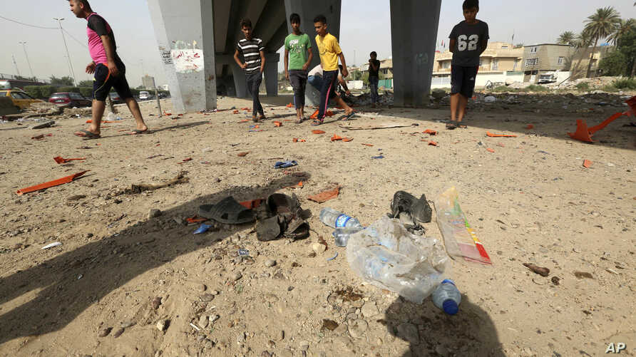 Civilians gather at the site of a suicide bomb attack in Baghdad's western Iskan neighborhood, Iraq, Oct. 29, 2016. Iraqi officials say a suicide bomber targeting Shiiite pilgrims has killed seven people and wounded more than 20 in the Iraqi capital,
