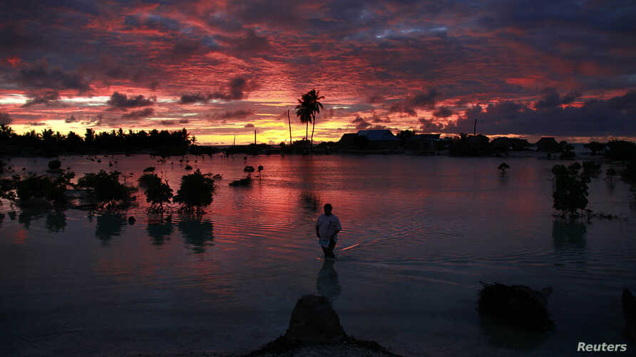 A villager wades through a small lagoon, which at high-tide laps at the base of homes, near the village of Tangintebu on South Tarawa in the central Pacific island nation of Kiribati,  which consists of a chain of 33 atolls and islands that stand jus...