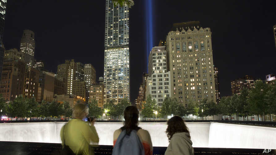 Visitors to the National September 11 Memorial observe the Tribute in Light, Monday, Sept. 8, 2014, in New York. The tribute, an art installation of 88 searchlights aiming skyward in two columns, is a remembrance of the Sept. 11, 2001, attacks. (AP P