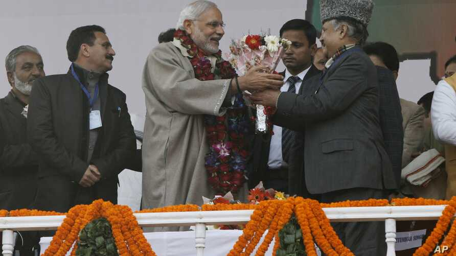 Indian Prime Minister Narendra Modi, center, is given flowers as he arrives for a campaign rally ahead of  local elections in Srinagar, in India-controlled Kashmir, Dec. 8, 2014.