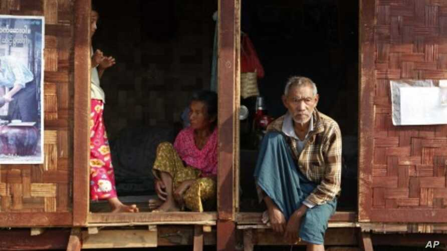 Ethnic Kachin people sit in the doorways of shelters at a temporary camp for people displaced by fighting between government troops and the Kachin Independence Army, or KIA, outside the city of Myitkyina in the north of the country, February 22, 2012