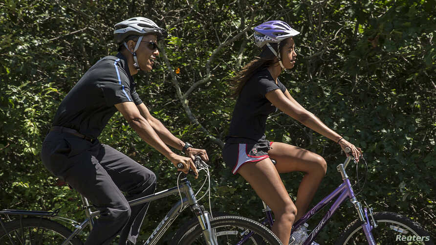 U.S. President Barack Obama cycles with his daughter Malia during their family vacation at Martha's Vineyard in Massachusetts,  Aug. 15, 2014.