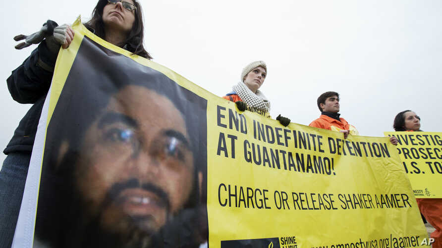 FILE - Human rights activists hold a banner with a picture of Shaker Aamer.