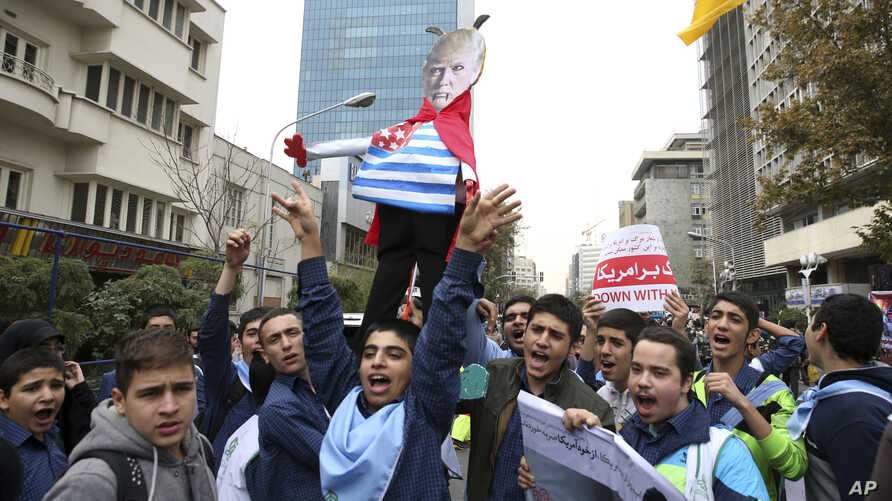 Iranian schoolboys chant slogans while holding an effigy of U.S. President Donald Trump in an annual gathering in front of the former U.S. Embassy marking the anniversary of its 1979 takeover, in Tehran, Iran, Nov. 4, 2017.