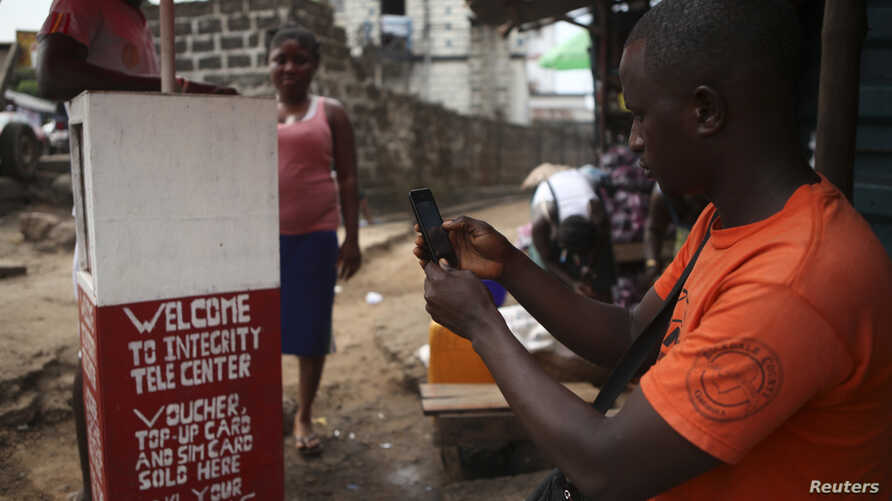 FILE - A man inspects a mobile phone at a 'telecenter' kiosk in Sierra Leone's capital, Freetown.