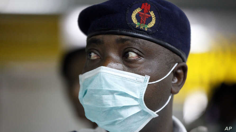 FILE - A Nigerian health official wearing a protective mask waits to screen passengers at the arrivals hall of Murtala Muhammed International Airport in Lagos, Nigeria, Monday, Aug. 4, 2014.