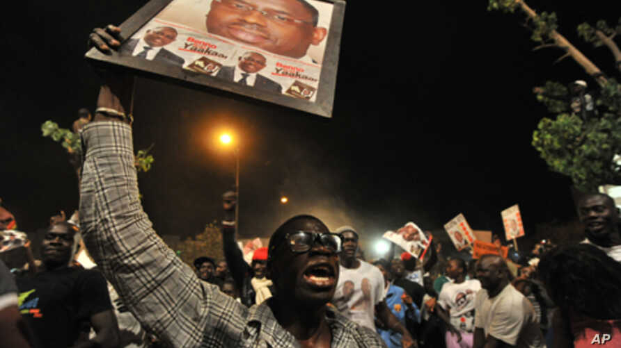 Supporters of Senegalese opposition challenger Macky Sall celebrate their candidates election victory in Dakar, March 25, 2012.
