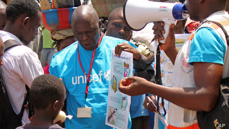 FILE - UNICEF health workers teach people about the Ebola virus and how to prevent infection, in Conakry, Guinea, March 31, 2014..