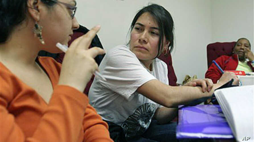 Theresa Rendon (C), originally from Mexico, now living in Queens borough of New York City and working as a housekeeper in New York, listens as Priscilla Gonzalez (L), a Domestic Workers United organizer, translates information from English to Spanish