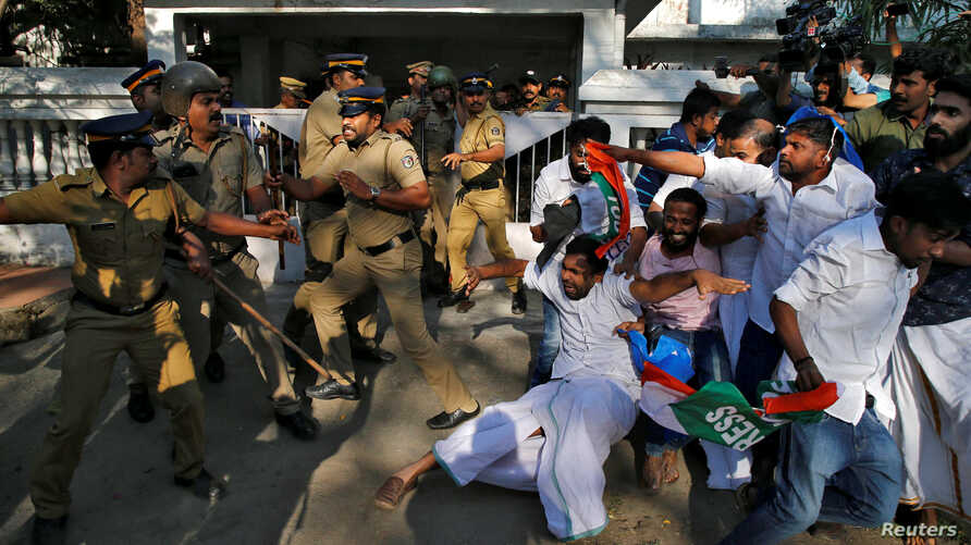 A police officer wields his stick against the members of Kerala Students Union (KSU), the student wing of India's main opposition Congress party, outside a police station during a protest in Kochi, India, Jan. 3, 2019.