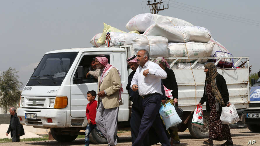 Kurdish refugees, heading home to Kobani, Syria, walk next to a truck full of their belongings on their way to a border gate in Suruc,Turkey, but many thousands are reluctant to return to a wasteland of collapsed buildings, April 20, 2015.