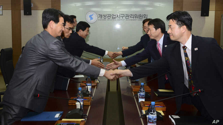 In this photo released by Unification Ministry, South Korean delegates, right, shake hands with their North Korean counterparts at the start of a meeting at Kaesong Industrial District Management Committee in Kaesong, North Korea, Sept. 11, 2013.
