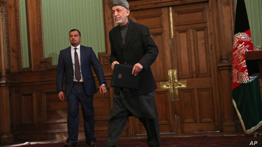 Afghan President Hamid Karzai leaves a press conference at the presidential palace in Kabul, Afghanistan, Saturday, Jan. 25, 2014.
