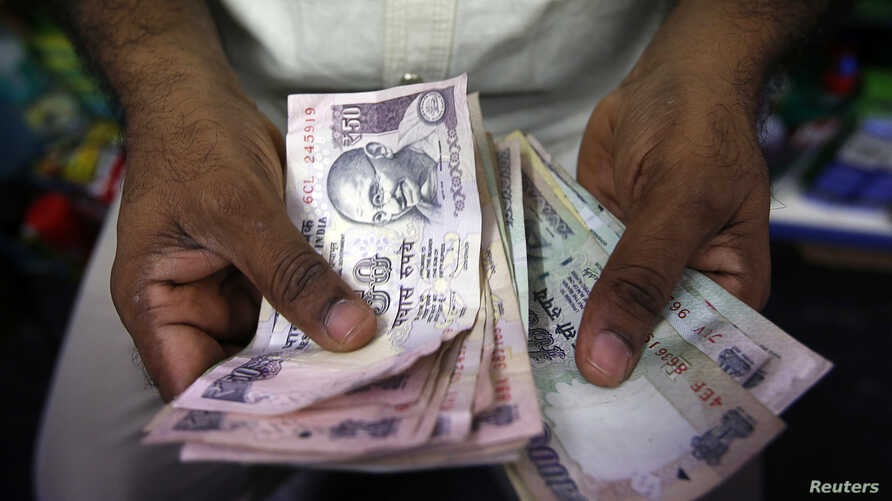 A private money trader counts Indian rupee currency notes at a shop in Mumbai, India, Aug. 1, 2013.