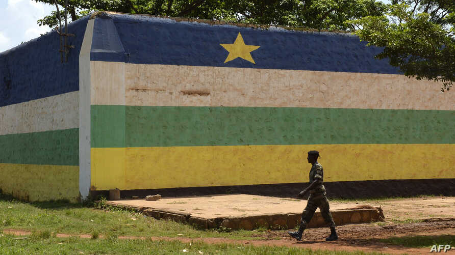 "FILE - A man walks in front of the jail of Bangui, ""Maison Centrale de Ngaragba,"" whose walls are painted with the colors of the flag of Central African Republic, April 22, 2014."