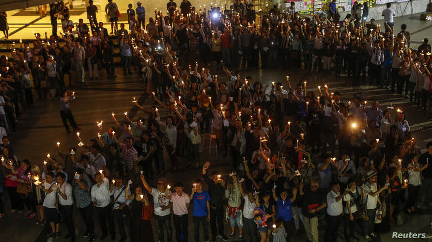 People hold candles as they form a peace sign during an anti-violence campaign in center of Bangkok, Thailand, Jan. 3, 2014.