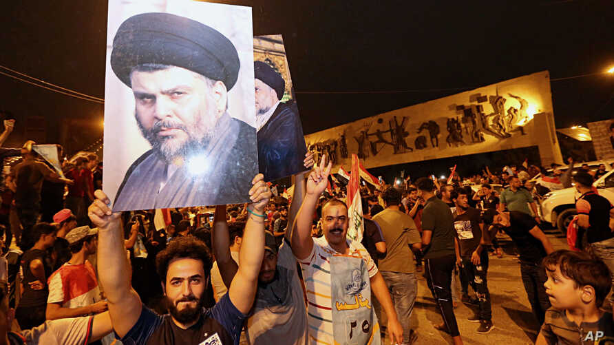 Followers of Shiite cleric Muqtada al-Sadr, seen in the posters, celebrate in Tahrir Square in Baghdad, Iraq, May 14, 2018. Iraq's electoral commission announced the Shiite cleric Muqtada al-Sadr as the early  front-runner.