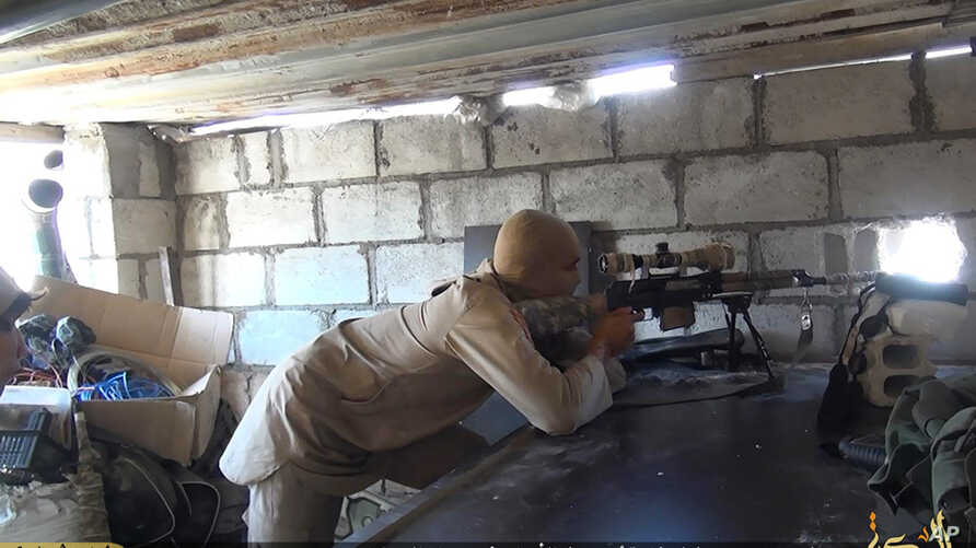 FILE - This file picture released on July 13, 2015 by the Rased News Network, a Facebook page affiliated with Islamic State militants, shows an Islamic State militant sniper in position during a battle against Syrian government forces, in Deir el-Zou