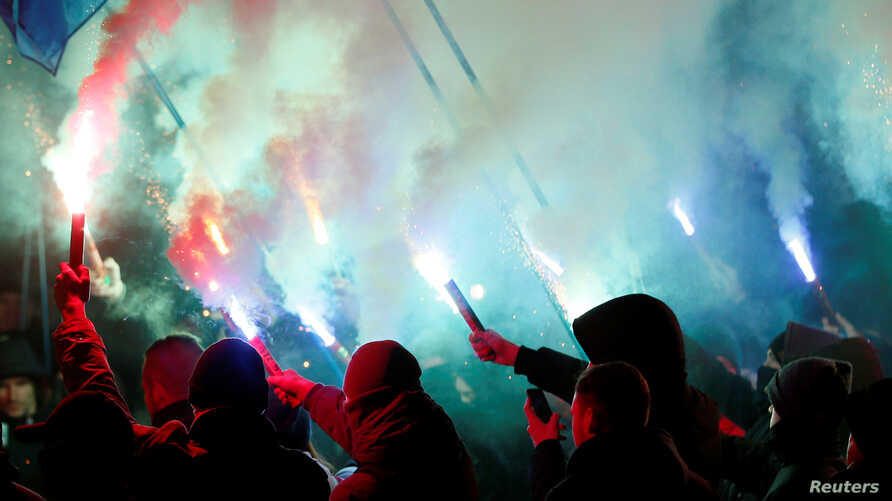 Activists of opposition parties burn flares during a rally demanding to break an agreement with Russia on the use of the Azov Sea and the Kerch Strait, in front of the parliament building in Kiev, Ukraine November 26, 2018.