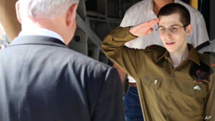 Gilad Shalit salutes in front of Israel's Prime Minister Netanyahu at Tel Nof air base, Oct 18, 2011