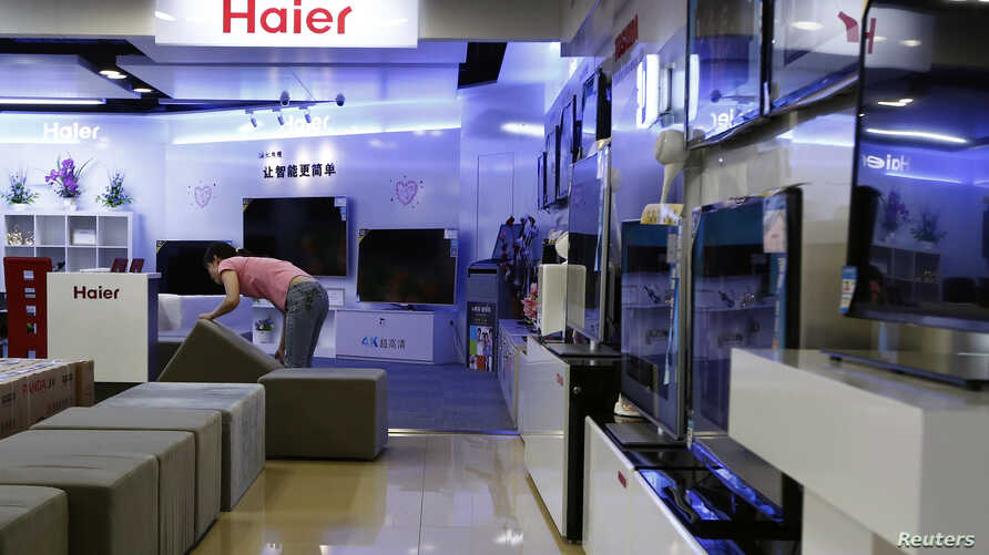 FILE - An employee arranges stools at a section displaying Haier television sets inside a Suning store in Shanghai.
