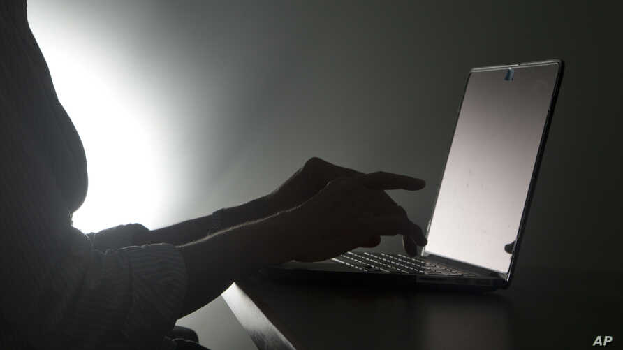FILE - A Dec. 12, 2016, photo illustration, shoes a person typing on a laptop, in Miami, Florida. A new survey shows that about one in four women that have been queried in eight different countries said they had experienced online abuse or harassment
