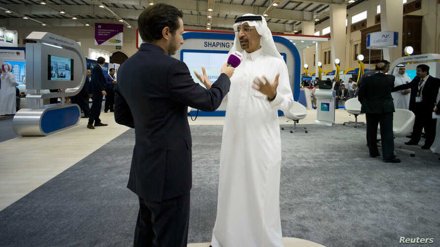 Saudi Aramco Chief Executive Officer Khalid al-Falih (R) speaks to a media member at the company's booth during Petrotech 2014 (a petrochemicals conference) at the Bahrain International Exhibition Center in Manama, May 19, 2014.