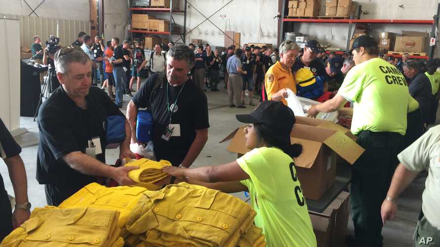Warren Heslip, 47, of Southland, New Zealand, receives a yellow firefighting shirt, Aug. 24, 2015 at the National Interagency Fire Center in Boise, Idaho.
