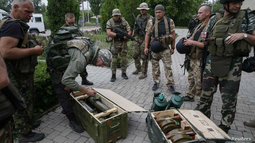 National guard soldiers inspect weapons captured from rebels in Slovyansk, Ukraine, July 6, 2014.