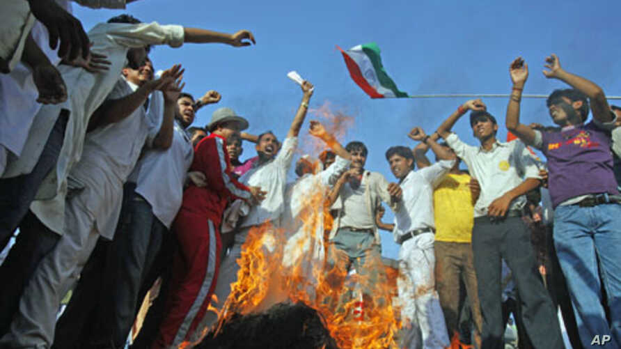 Supporters of India's yoga guru Swami Ramdev shout anti-government slogans as they burn an effigy of Indian Prime Minister Manmohan Singh outside the ashram, a spiritual retreat, of Ramdev in the northern Indian town of Haridwar, June 10, 2011
